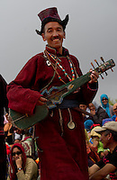 Men performing the traditional dance to the music of their traditional banjo-guitars while wearing their traditional Goncha robes, hats and sashes.