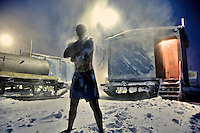 A man, working for oil and gas exploration company Siesmorevzedka rubs himself with snow during sauna in a camp in the Arctic tundra. The sauna's water is heated by the diesel tank on the left of the picture. /Felix Features