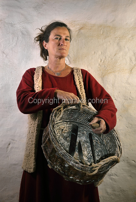 Aurelie Paillard, basketmaker at the Guedelon project since 28/03/2011, wearing medieval costume and carrying a basket and tools, at the Chateau de Guedelon, a castle built since 1997 using only medieval materials and processes, in Treigny, Yonne, Burgundy, France. The Guedelon project was begun in 1997 by Michel Guyot, owner of the nearby Chateau de Saint-Fargeau, with architect Jacques Moulin. It is an educational and scientific project with the aim of understanding medieval building techniques and the chateau should be completed in the 2020s. Picture by Manuel Cohen