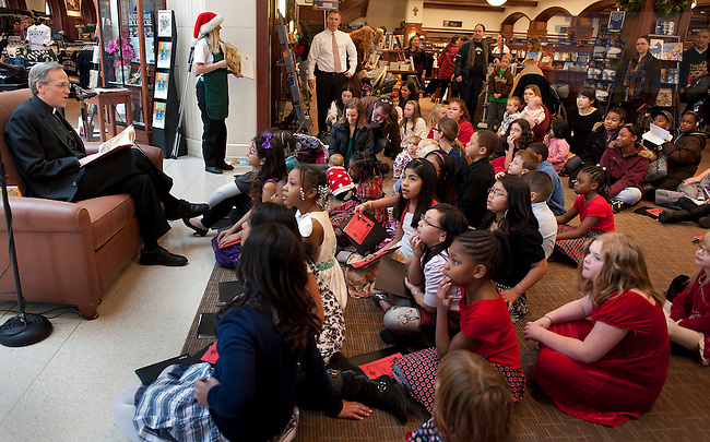 December 17, 2011; President Rev. John I. Jenkins, C.S.C., reads to children at the Hammes Bookstore. Photo by Barbara Johnston/University of Notre Dame.