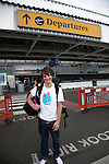 Young man with rucksack outside Departures, Heathrow airport, London, England Model released teenager with rucksack  Heathrow airport departures
