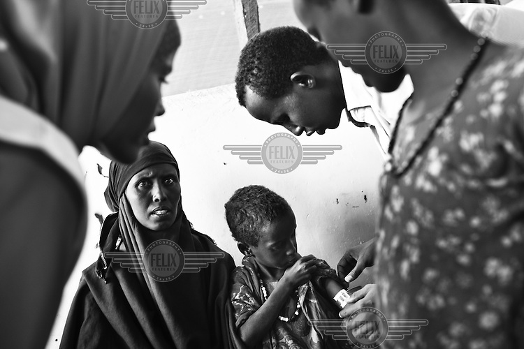 MSF doctors check 7 year old Fatima Mohammed who weighs just 12 kgs, (half the recommended weight of a child her age, and the typical weight of a child of around 2 in the UK) at the MSF registration centre at the Dagahaley camp part of the Dadaab refugee camp in Kenya. The drought is the worst in East Africa for 60 years. The UN described it as a humanitarian emergency. The already overcrowded complex received 1,000 new refugees a day in June, five times more than a year ago. About 30,000 people arrived at the Dadaab refugee camp in June, according to UNHCR compared to 6,000 in June 2010.