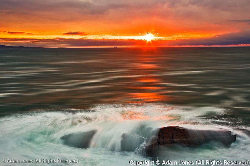 Waves crashing against granite coastline at sunset, Acadia National Park, Maine