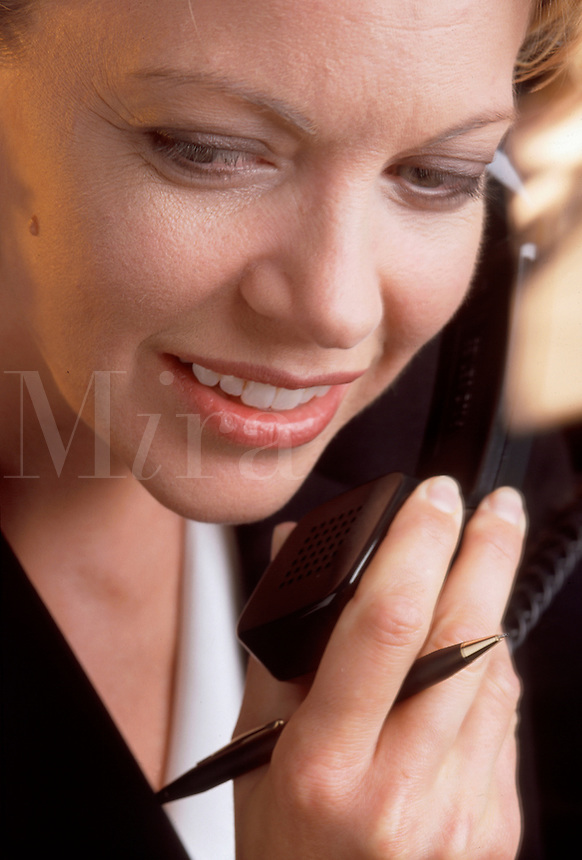 A smiling business woman talking on the phone.
