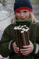 Kinder bauen Vogel-Nistkasten für Meisen, Vogelnistkasten, Nistkasten, Kind zeigt auf gleiche Länge gesägte Stäbe aus Haselnuss-Ästen