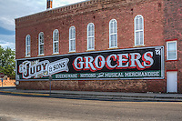 J.M. Judy &amp; Sons  Mural in Atlanta Illinois on Route 66.<br /> During the 1890s J.M.Judy operated his grocery store on the first floor of this, the Union Hall Building. As the 70   x 15   mural attests, Mr.Judy also dealt in Queensware, a popular china pattern of the day, notions, and musical merchandise.&nbsp;<br /> <br /> Bill Diaz of Pontiac, Illinois created this design using a photo taken in the early 1900s of the original J.M.Judy &amp; Sons mural that adorned this side of the building.&nbsp;<br /> <br /> The  J.M.Judy &amp; Sons   mural was completed in June 2002 during the  Rt.66 Firecracker Walldog Jam   gathering of approximately 35 Letterheads in Atlanta.