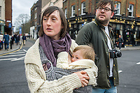 A mother breastfeeds her 15 month old boy from a sling while crossing a busy road with her partner.<br /> <br /> London, England, UK<br /> 22-03-2015<br /> <br /> &copy; Paul Carter / wdiip.co.uk