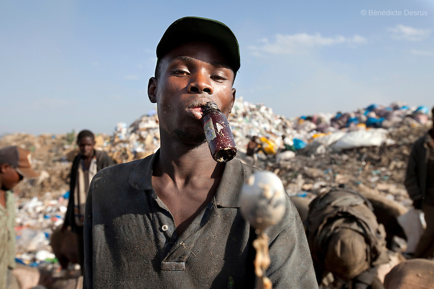 13 february 2013 - Dandora dumpsite, Nairobi, Kenya - A boy sucks on a plastic bottle of noxious yellow glue at the Dandora dumpsite, one of the largest and most toxic in Africa. Located near slums in the east of the Kenyan capital Nairobi, the open dump site was created in 1975 and covers 30 acres. The site receives 2,000 tonnes of unfiltered garbage daily, including hazardous chemical and hospital wastes. It is a source of survival for many people living in the surrounding slums, however it also harms children and adults' health in the area and pollutes the Kenyan capital. Photo credit: Benedicte Desrus