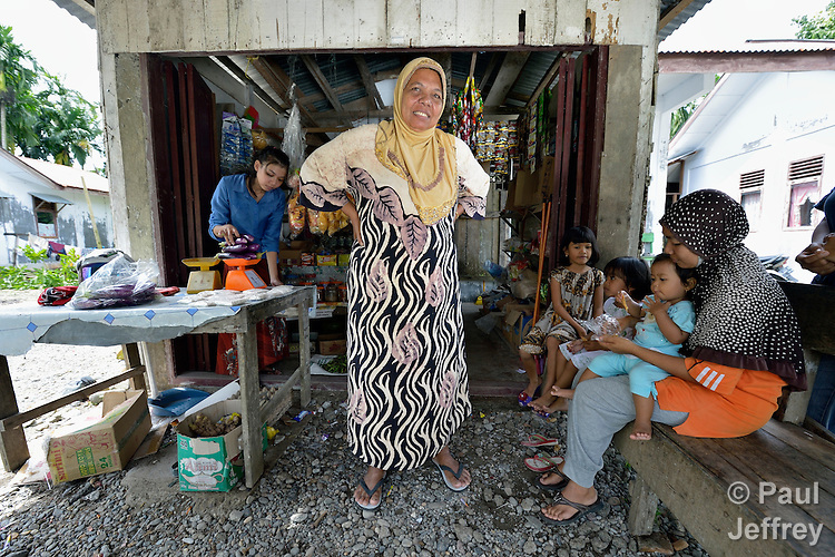 Nyak Minah stands in front of a store that she added to the front of her home in Kubang Gajah in Indonesia's Aceh province. After the 2004 tsunami, the U.S.-based Catholic Relief Service built her new house. She has since added on to it, including the small store where she sells basic food items.