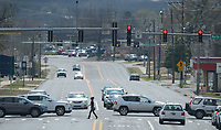 NWA Democrat-Gazette/ANDY SHUPE<br /> A pedestrian crosses School Avenue Friday, March 23, 2018, as traffic passes on Martin Luther King Jr. Boulevard in Fayetteville. Consulting firm Nelson/Nygaard wrapped up a nearly 2-year-long study on all modes of travel in the city and presented its findings to the City Council on Tuesday.