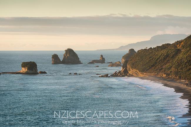 Rock formations and sunset on coastline near Greymouth, West Coast, Buller Region, New Zealand