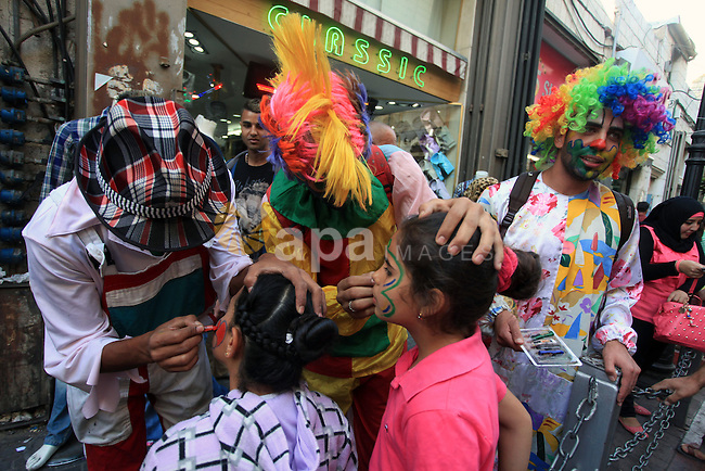 Palestinian clowns draw on children's faces at a street market ahead of the Muslim festival Eid al-Adha in the West Bank city of Ramallah, on Oct. 14, 2013.  Eid al-Adha (the Festival of Sacrifice) is celebrated throughout the Muslim world as a commemoration of Abraham's willingness to sacrifice his son for God, and cows, camels, goats and sheep are traditionally slaughtered on the holiest day. Photo by Issam Rimawi