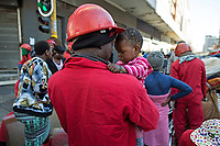 During an eviction, Red Ant William Mahlalela plays with S'nehlanhla Fortunate Majoro as her mother atempts to gather together some of her belongings after they were evicted from Fatti's Mansions in Johannesburg. <br />
