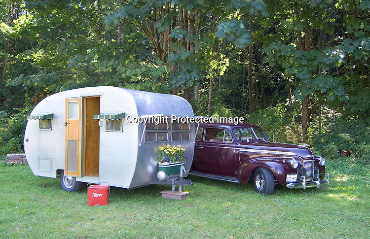 Silver 1951 Comet canned ham vintage travel trailer. Parked alongside is a black cherry 1940 Chevrolet two door sedan master deluxe.