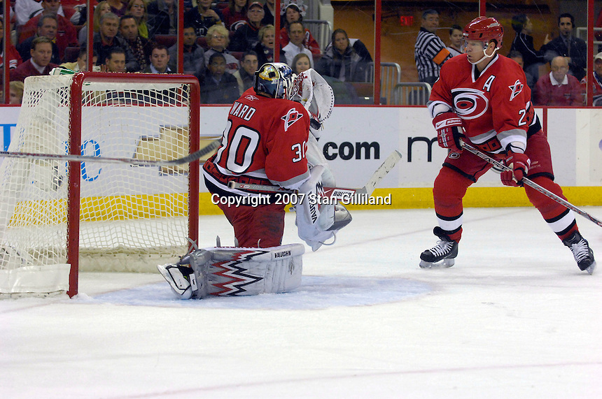 Carolina Hurricanes' goalie Cam Ward (30) makes a save against the Toronto Maple Leafs as teammate Glen Wesley watches Tuesday, Jan. 30, 2007 at the RBC Center in Raleigh. The Leafs won 4-1.