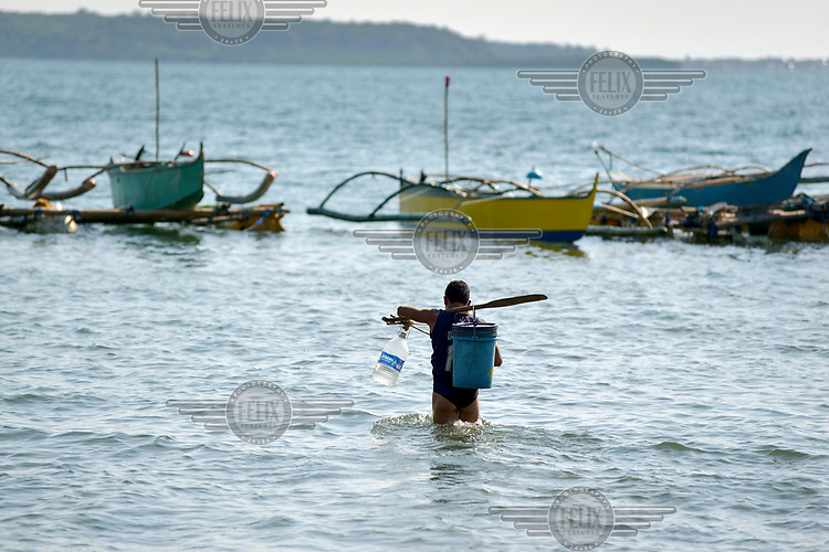 A fisherman heads out to his boat at the beginning of a coastal expedition. The Chinese occupation of the Scarborough Shoal has deprived Masinloc's fishermen of one of their most productive fishing grounds, limiting them to coastal waters.