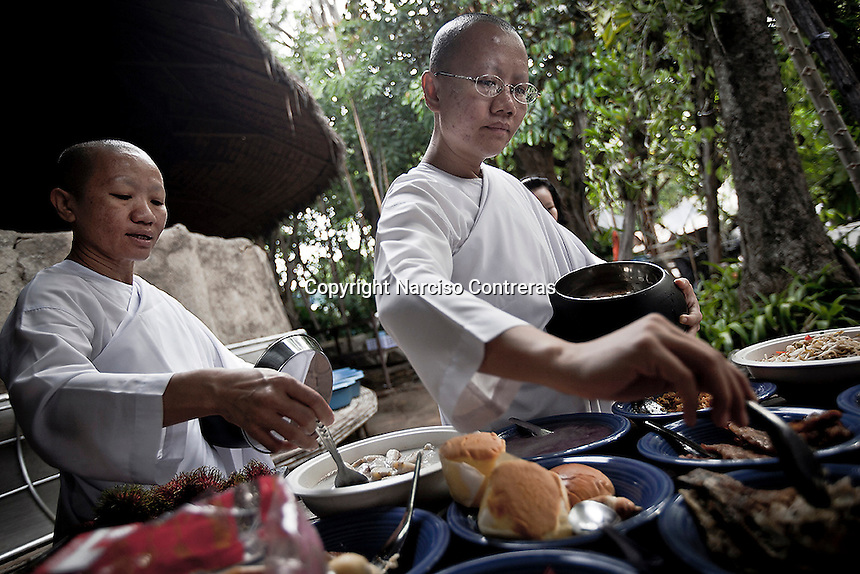 Mae chees gather all together to share the food gotten from charity collected at the neighborhood streets. The mae chii are the most numerous group of Thai Buddhist renunciant women.They observe eight precepts: to abstain from killing living beings; to abstain from taking what has not been given; to abstain from sexual activity; to abstain from lying speech; to abstain from drinking liquor or taking anything that may intoxicate the mind; to abstain from eating after noon; to abstain from watching dancing, singing, shows and from adorning oneself; to abstain from using a high bed.