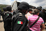 Activists of the Humanitarian caravan to San Juan Copala are surrounded by state policemen on the highway Juxtlahuaca-San Juan Copala, June 08, 2010, as the state authorities try to stop the caravan. More than four hundred people make their way to San Juan Copala's Autonomous Municipality, carrying 35 tons of food to the Triqui people of San Juan Copala sieged by the paramilitaries of the ruling party PRI's Union para el Bienestar Social de la Region Triqui (UBISORT). Photo by Heriberto Rodriguez