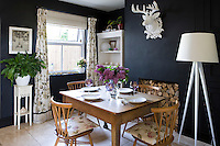 The black-painted walls create a feeling of intimacy in the dining room and serve as a backdrop for a collection of vintage furniture