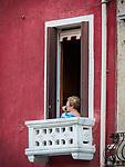 A woman sits on her balcony above Fondamenta dei Vetrai on the main canal of Murano, Italy