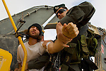Two border polices officers search an Israeli activist chained to an Israeli bulldozer at a construction site for Israel's controversial West Bank barrier in the village of Al Walaja on 09/06/2010. The officers were searching for the key to the lock the activist used to chain himself to the bulldozer.