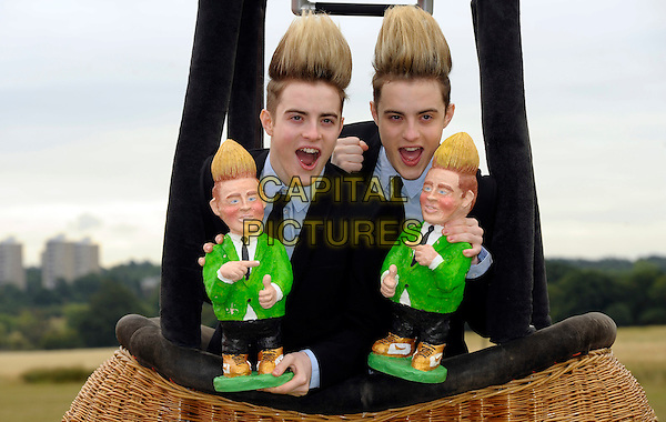 JEDWARD .John & Edward Grimes launching Rowntree's Randoms Foamy Gnome on the Roam tour, Richmond Park, London, England. .August 12th, 2010 .twins brothers family half length black jacket suit blue shirt hair dolls mouth open basket hot air balloon .CAP/CJ.©Chris Joseph/Capital Pictures.