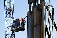 Bouwvakker brengt een beschermende laag aan op een damwand , voordat deze wordt geplaatst