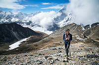A trail runner standing and resting while starting up the first pass, Kongma La, above Chukhung while starting the 3 Passes tour, with a view of Ama Dablam in the background. Khumbu Valley, Nepal.