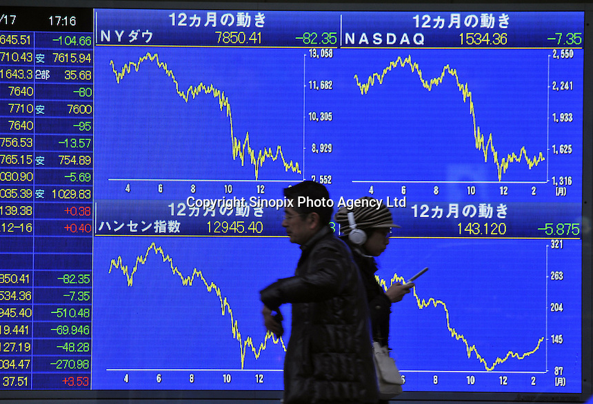 Locals pass a stock exchange board in down-town Tokyo. Japan is suffering the biggest shrinking of its economy for 35 years. Shares in Tokyo slumped to their lowest in almost four months, as financial shares such as banks and property firms slid on continued credit worries. .