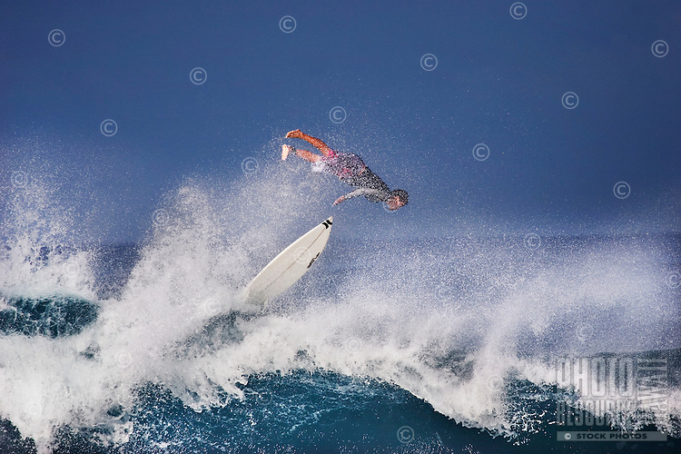 Surfer wipe outs on a large winter wave at Banzai Pipeline on North Shore of Oahu.