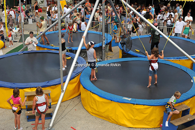 Children jump on bungee-equipped trampolines at the Wisconsin State Fair in West Allis, Wisconsin on August 3, 2008.