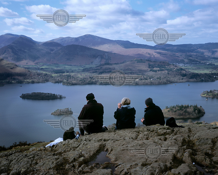 Tourists take in the view at Walla Crag looking out over Derwentwater near Keswick, Cumbria.