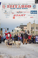 Rob Cooke and team leave the ceremonial start line with an Iditarider at 4th Avenue and D street in downtown Anchorage, Alaska during the 2015 Iditarod race. Photo by Jim Kohl/IditarodPhotos.com