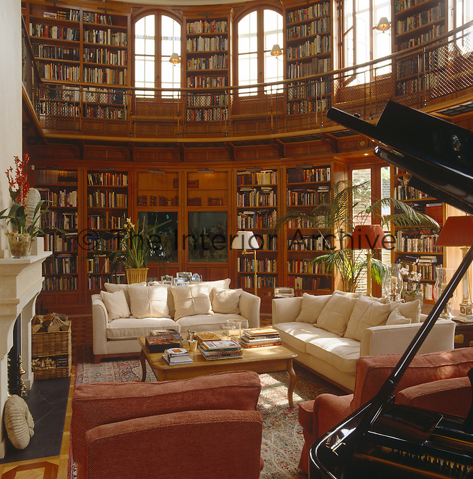 Double-height library furnished with white sofas and a grand piano