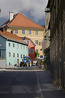 Blue tractor and trailer driving along narrow village road passing pastel painted buildings. Imst district,Tyrol, Austria.