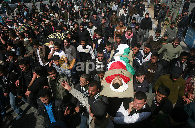 Palestinian mourners carry the bodies of seven Islamic Jihad militants (not all seen in picture), who were killed in Israeli air strikes, during their funeral in Gaza City on March 10, 2012. Twelve Palestinian fighters were killed and at least 20 people wounded in a series of Israeli air strikes on the Gaza Strip, Palestinian medics said. Photo by Ashraf Amra