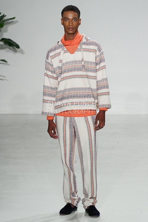 Model walks runway in an ecru stripe drug rug, orange turtleneck and ecru stripe como trouser, from the Palmiers du Mal Spring Summer 2017 collection by Brandon Capps and Shane Fonner, at Skylight Clarkson Square on July 14 2016, during New York Fashion Week Men's Spring Summer 2017.