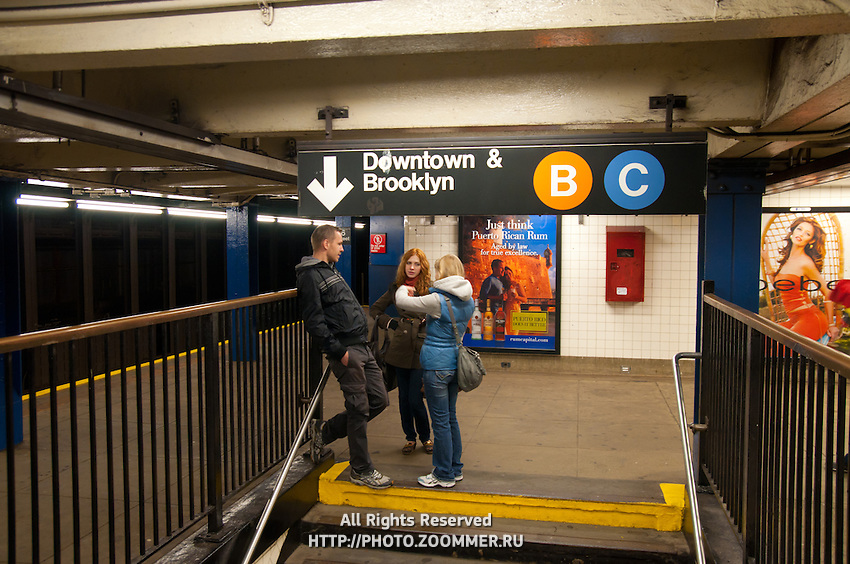 Three people talking in subway station near the sign