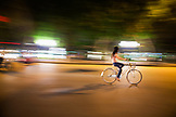 VIETNAM, Hanoi, a young woman rides her bike down a busy street at night, Hoan Kiem Lake in the distance