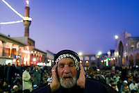 Baghdad, Iraq, March 14, 2003.A man chants  a Coran surat just before the Friday evening prayer in Al Khaddamein mosq, one of the most important Shia'i shrines in Iraq.