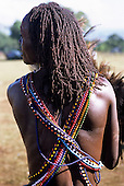 Lolgorian, Kenya. Young Moran Siria Maasai with colourful bead necklaces with scars from a lion mauling him on his back.