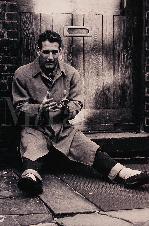 Actor Paul Newman sits on a doorstep and talks passionately as he gestures. Circa 1956.
