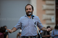 """Matteo Orfini MP.<br /> <br /> Rome, 27/07/2020. Today, hundreds of people, NGO's (ONG) representatives, actors and politicians gathered in Piazza San Silvestro (near the Italian Parliament) to protest (1.) against the dramatic situation in Libya - erupted in a civil war between the GNA (2.) and the forces of General Khalifa Belqasim Haftar - and to protest against the inhumane conditions of migrant people trapped in legal and illegal prisons in Libya. The aim of the demo was to call the Italian Government to stop funding the """"Libyan Coast Guard"""" and to immediately help and free People in Libya throughout """"Humanitarian Corridors"""", and give them the protection they are entitled of by the International Human Rights Conventions. <br /> From the organisers Facebook event page: «[…] we meet to ask the Italian Government and the European States to stop funding the so-called Libyan coast guard, to close and evacuate the detention centres by transferring migrants out of Libya and to promote corridors to help people on the run find protection without endangering their lives. The men, women and children who take the sea from the Libyan coast flee from situations of extreme misery, despotic regimes, tribal persecutions, ethnic conflicts, wars and environmental catastrophes. And in Libya they are subjected to violence, extortion, detention, torture, rape and torture. A few days ago, on July 16, the Chamber of Deputies [Of the Italian Parliament, ndr] for the fourth consecutive year approved the financing of the Italian mission in Libya, which provides financial support for the so-called Libyan coastguard and training and training of its members. […] The mobilization will be accompanied by readings by Ascanio Celestini, Valentina Carnelutti, Fabrizio Gifuni and Sonia Bergamasco […]».<br /> <br /> Footnotes & Links:<br /> 1. https://www.facebook.com/events/2732849460337428/<br /> 2. 07.05.19 Prime Minister of Libya Fayez al-Serraj Met Italian PM Giuseppe Conte at Palazzo Chigi ht"""
