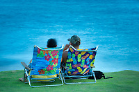 Couple on beach chairs in Poipu. Kauai, Hawaii