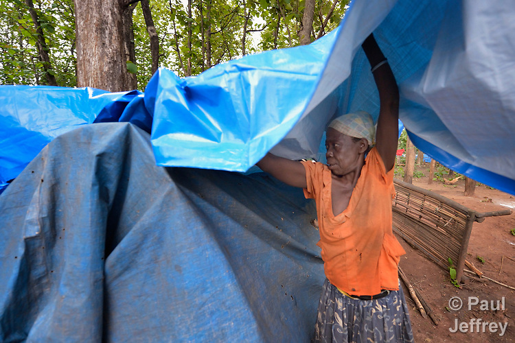 A woman places a new tarp atop her leaky shelter in a camp for more than 5,000 displaced people in Riimenze, in South Sudan's Gbudwe State, what was formerly Western Equatoria. Families here were displaced at the beginning of 2017, as fighting between government soldiers and rebels escalated.<br />