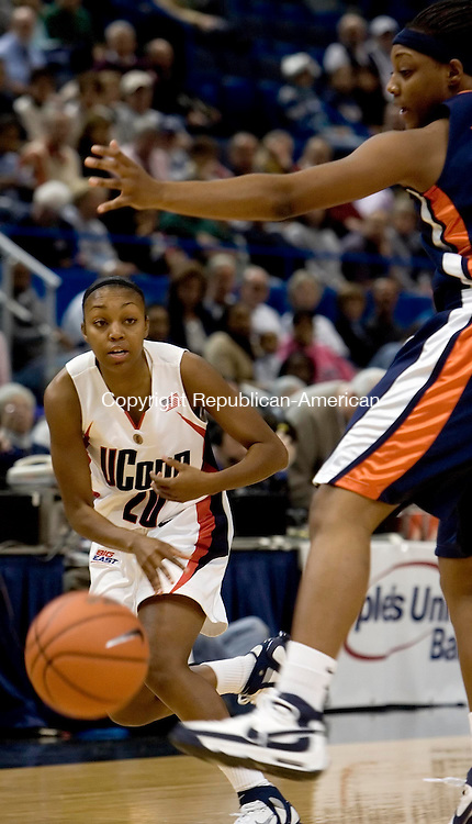 HARTFORD --05 DECEMBER 2007-120507JS07-UConn's Renee Montgomery (20) bounces a pass inside past Virginia's Monica Wright (22)<br /> during their game Monday at the Hartford Civic Center.<br />  Jim Shannon/Republican-American