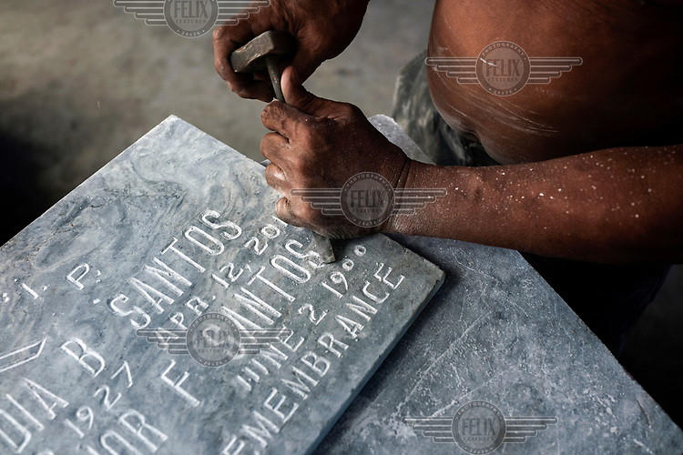 A man chisels words and numbers into a headstone in Manila North Cemetery.  Manila North Cemetery is home to thousands of 'informal settlers' who have built shacks using in and around the mausoleums, crypts and tombs. In comparison to the city's dangerous shantytowns the cemetery is relatively quiet and safe. However, water must be collected from a few public wells and the electricity supply is erratic, usually stolen from mains cables. In the summer the sweltering heat drives people to sleep outside often on top of the tombs.<br /> <br /> Some of the residents live in the crypts and mausoleums of wealthy families, who pay them a stipend to clean and watch over them. Others make a living carving headstones or selling candles to visitors and helping out at funerals as the daily life of the cemetery goes on around the people who live there.