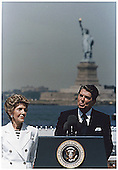 U.S. President Ronald Reagan gives a speech on the Centennial of the Statue of Liberty, Governor's Island, New York on July 4, 1986.  At left is First Lady Nancy Reagan.<br /> Credit: White House via CNP