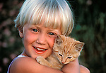 smiling young girl holding kitten