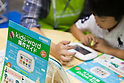 A boy tries a Casio's kids-word electronic dictionary during the Tokyo International Book Fair at Tokyo Big Sight on September 25, 2016. The 23rd edition of Tokyo International Book Fair (TIBF) attracted 470 exhibitors and approximately 40,000 visitors over the three days from September 23 to 25. (Photo by Rodrigo Reyes Marin/AFLO)